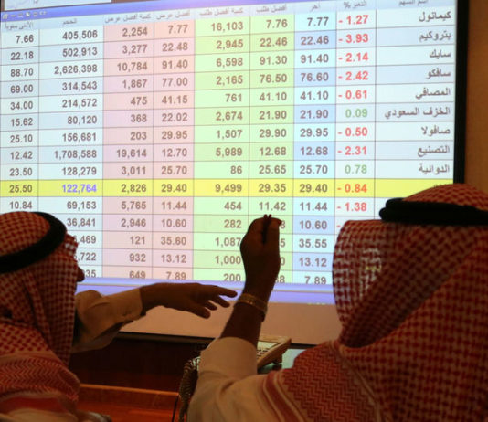 © Reuters. Saudi men look to a screen showing stock prices at ANB Bank, in Riyadh